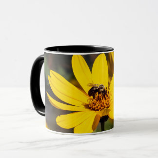 Abeille d'extraction sur la tasse de café jaune de