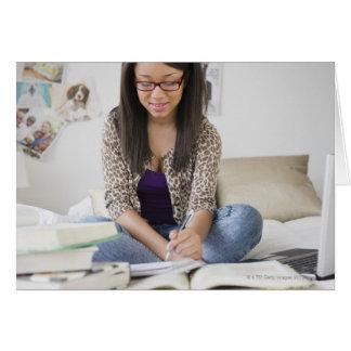 Adolescente de métis faisant le travail sur le lit carte de vœux