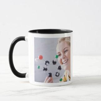 Adolescente regardant le modèle de molécule mug