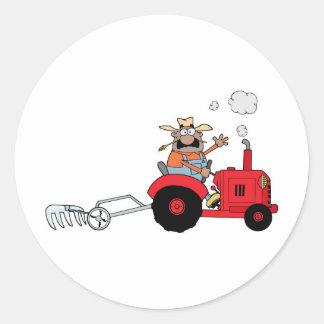 Agriculteur heureux à l'aide d'un tracteur adhésifs ronds
