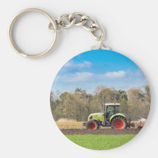 Agriculteur sur le tracteur labourant le sol porte-clés