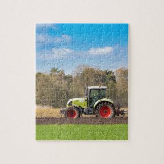 Agriculteur sur le tracteur labourant le sol puzzle