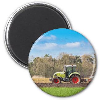 Aimant Agriculteur sur le tracteur labourant le sol