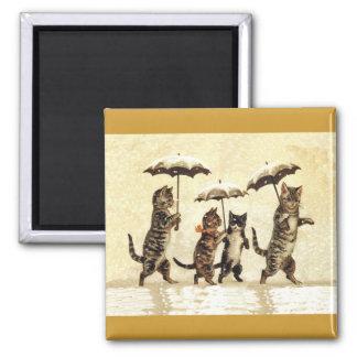 Aimant Famille de chat avec des parapluies marchant dans