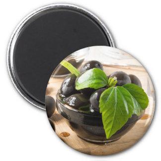 Aimant Olives noires sur une table et des tasses en verre