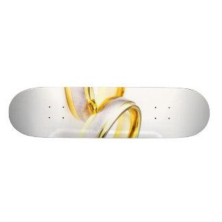 Anneaux de mariage d'or sur l'arrière - plan blanc skateboard