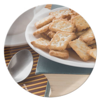 Assiettes En Mélamine Plat blanc avec des biscuits sur le vieux livre