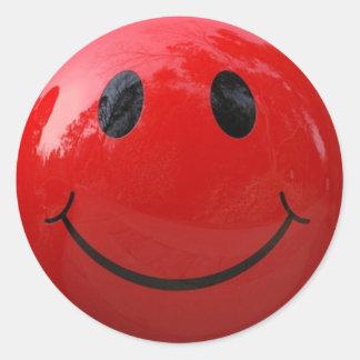 Autocollant souriant rouge brillant de visage