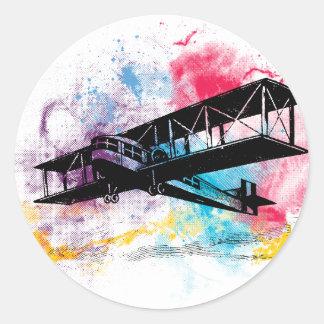Avions vintages avec les nuages colorés adhésif rond