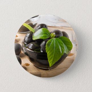 Badge Olives noires sur une table et des tasses en verre