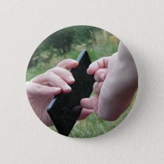 Badge Rond 5 Cm Mains femelles touchant l'écran d'un smartphone