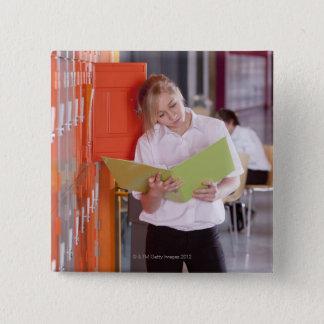 Badges Étudiant enlevant le classeur du casier d'école