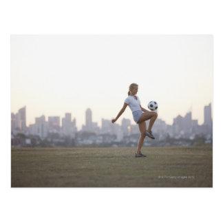 Ballon de football kneeing de femme en parc urbain carte postale
