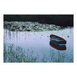 Bateau à rames sur le petit lac entouré par l'eau photographe