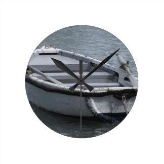 Bateau d'aviron en bois simple sur la mer horloge ronde