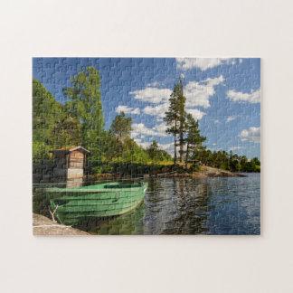 Bateau vert dans un fjord dans le puzzle denteux