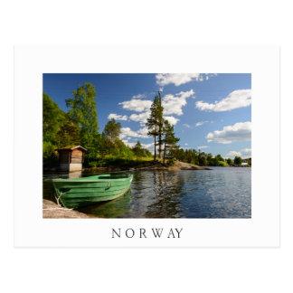 Bateau vert dans un fjord en carte postale de