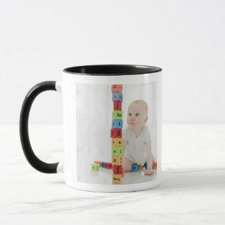 Bébé sur le plancher regardant les blocs en bois mug