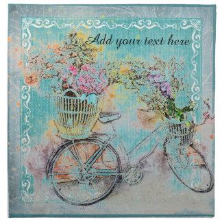 Bicyclette avec des paniers de fleur sur la toile serviettes en tissus