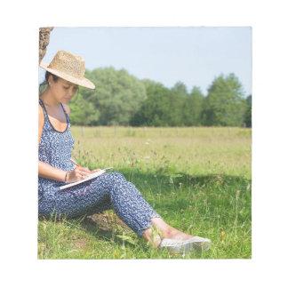Bloc-note Femme s'asseyant contre l'écriture d'arbre dans