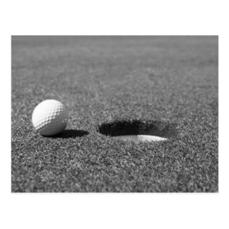 Boule de golf près de trou carte postale