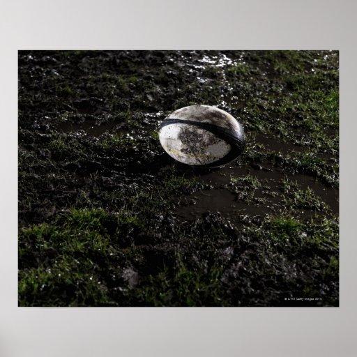 Boule de rugby boueuse se reposant sur mâché vers  poster