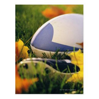 Boule et chaussure de rugby sur la pelouse en carte postale