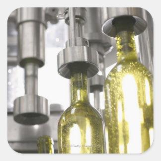 bouteilles de vin étant remplies du vin à l'usine sticker carré