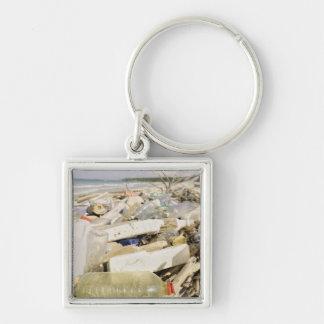 Bouteilles en plastique et océan vidant sur un porte-clé carré argenté