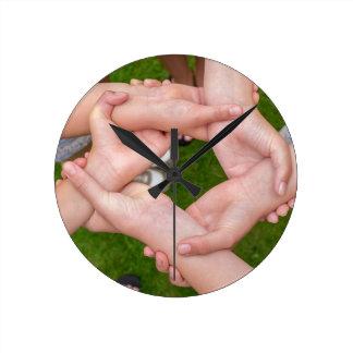 Bras avec des mains des filles se tenant horloge ronde