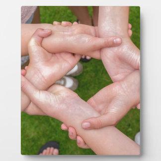 Bras avec des mains des filles se tenant impression sur plaque