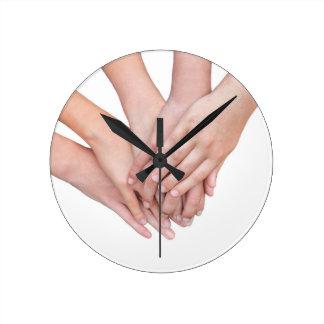 Bras des mains de filles sur l'un l'autre horloge ronde