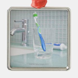 Brosse à dents dans une tasse dans la salle de ornement carré argenté