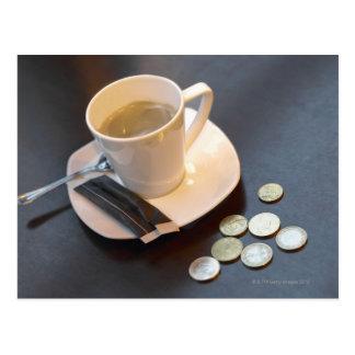 Café et argent sur une table carte postale