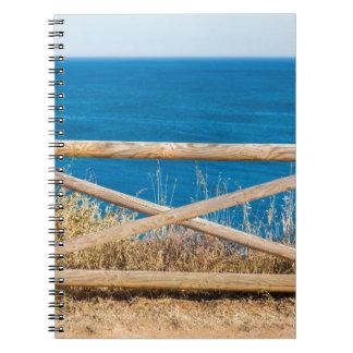 Carnet Barrière en bois à la côte avec sea.JPG bleu