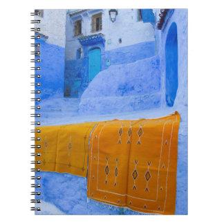 Carnet Couvertures drapées sur un mur bleu