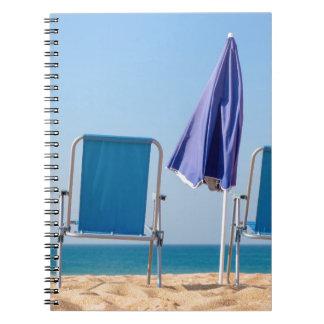 Carnet Deux chaises et parasols de plage bleus à sea.JPG