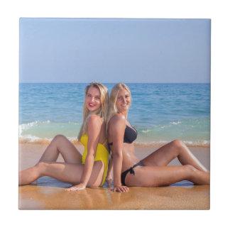 Carreau Deux filles s'asseyent sur la plage près de
