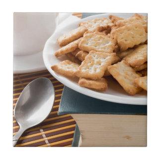 Carreau Plat blanc avec des biscuits sur le vieux livre