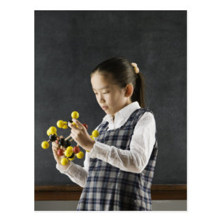 Carte Postale Fille asiatique regardant le modèle de molécule