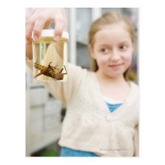 Carte Postale Fille regardant l'insecte dans le pot dans la