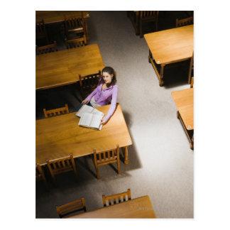 Carte Postale Livre de lecture de femme dans la bibliothèque