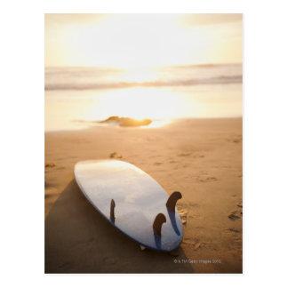 Carte Postale Planche de surf s'étendant sur la plage au coucher