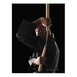 Carte Postale Studio tiré de l'homme s'exerçant avec le nunchaku