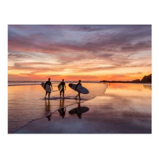 Carte Postale Surfers au coucher du soleil marchant sur la
