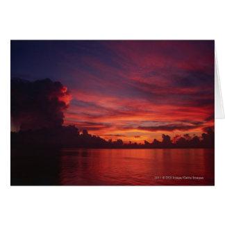 Cartes Coucher du soleil en mer avec les nuages foncés