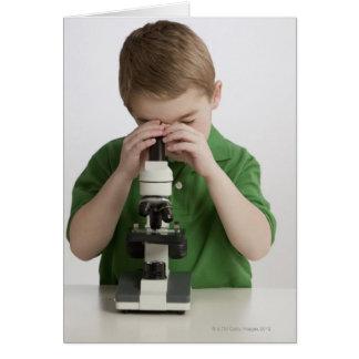 Cartes Garçon caucasien scrutant dans le microscope