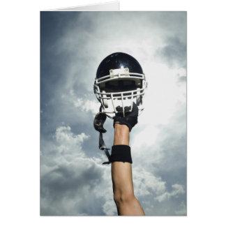Cartes Joueur de football tenant le casque en air