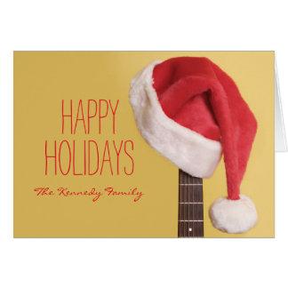 Cartes Un casquette de Père Noël accroche sur une guitare