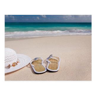 Casquette et sandales sur la plage tropicale carte postale